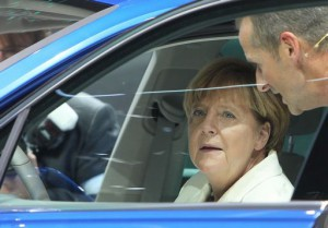 German Chancellor Angela Merkel sits on the driver's seat of a Tiguan GTE Plugin Hybrid car during her visit of the booth of German carmaker Volkswagen on the opening day of the Frankfurt Motor Show IAA in Frankfurt, western Germany, on September 17, 2015. AFP PHOTO / DANIEL ROLAND