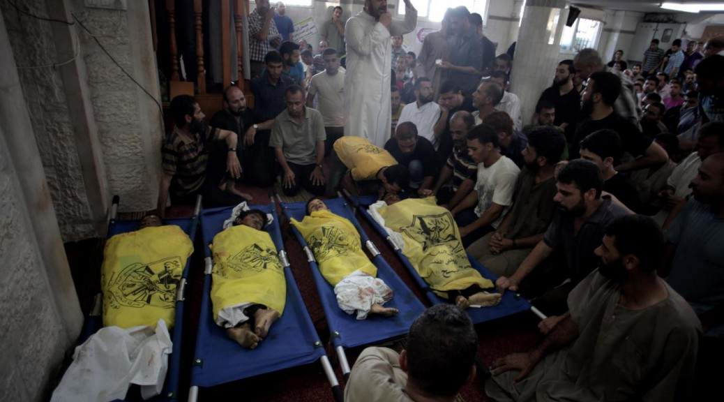 Palestinians mourn over the lifeless bodies of four boys from the same extended Bakr family, covered with yellow flags of Fatah movement, in the mosque during their funeral in Gaza City, Wednesday, July 16, 2014.  The four boys, who were cousins and ages 9 to 11, were killed while playing on a beach off a coastal road west of Gaza City, said Ashraf Al Kedra, a Palestinian doctor. Seven others _ adults and children _ were wounded in the strike, he said. (AP Photo/Khalil Hamra)