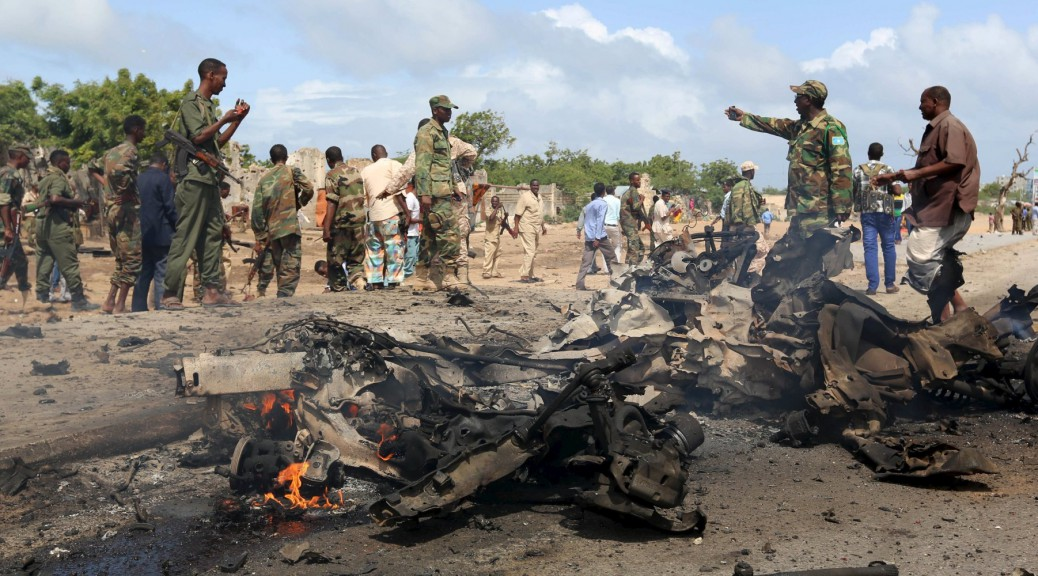 Somali government forces assess the scene of a car bomb attack in Hodan district in the capital Mogadishu June 24, 2015. A car bomb targeting a convoy of military instructors from the United Arab Emirates exploded in the Somali capital of Mogadishu on Wednesday, killing at least three Somalis but injuring no UAE citizens, security officials said. REUTERS/Feisal Omar